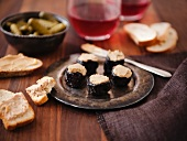 Prunes Stuffed with Foie Gras on a Metal Dish; Bread and Foie Gras; Pickles; Wine