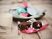Mini Cream Filled Chocolate Cakes in Colored Foil Wrappers with a Glass of Milk