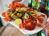 A mixed appetizer platter with ham and salami