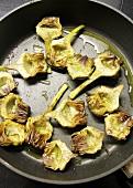 Fried artichoke hearts in a pan