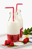 Layered raspberry milk in glass bottles