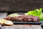 Beef steak with herb butter and pink pepper (close-up)