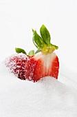 Half a strawberry in a pile of sugar