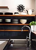 Küchenregal vor dunkelgrauen Wandfliesen neben Edelstahlspüle