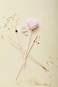 A heart-shaped cake pop and wooden sticks