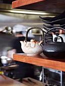 Teekannen und schwarzes Geschirr auf Edelholzregal