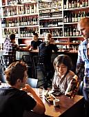 Gäste und Kellner in japanischem Restaurant; im Hintergrund ein grosses Wandregal mit Sakeflaschen
