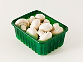 Fresh button mushrooms in a plastic punnet
