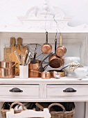 Various copper pots and kitchen utensils on a white wooden dresser