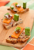 Slices of bread topped with mimolette, pesto gouda and fig chutney