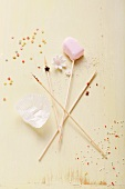 A heart-shaped cake pop and four wooden sticks