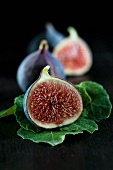 Fresh figs, whole and halved, and fig leaves