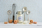 A whisk, a silver spoon, a flip-top jar, semolina and biscuits
