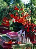 Gartentisch mit Kuchen und Gläsern und rote und orangefarbene Girlanden-Begonien