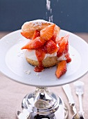 A scone topped with cream and strawberries