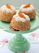 Mini carrot cakes topped with cream and marzipan carrots