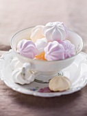 Various coloured meringues in a cup and on a saucer