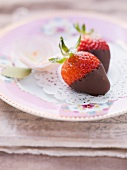 Chocolate strawberries on a pink, floral-patterned plate