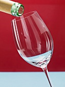 Wine being poured into a white whine glass