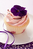 A cupcake decorated with a pansy