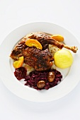 Roast goose with red cabbage with chestnuts, caramelised apple wedges and potato dumplings
