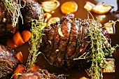 Roast venison with root vegetables and thyme in a pan