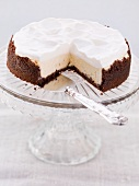 Chocolate cheesecake topped with cream, sliced