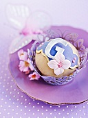 A cupcake with purple decoration on a purple plate