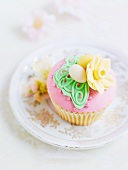 A cupcake decorated with pick frosting and marzipan decorations