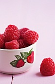 Fresh raspberries in a bowl with a strawberry picture