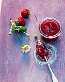 Strawberry and rose jam on a spoon and in a jar