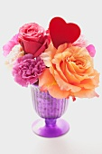 Various flowers and a heart in a purple vase