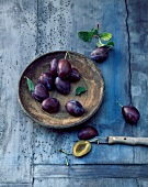 Plums in a wooden bowl and knifes