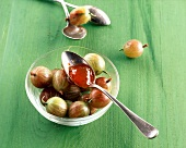 Gooseberry preserve with elderflowers on a spoon