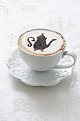 A cappuccino with a pattern stencilled in cocoa powder