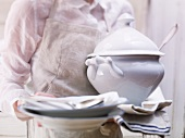 A man holding a soup tureen, crockery and cutlery