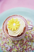 A cupcake decorated with light frosting and a marzipan flower in a cup