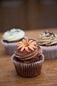 A chocolate cupcake decorated with a marzipan flowers