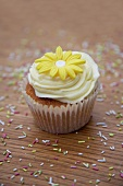 A cupcake decorated with light frosting and a marzipan flower