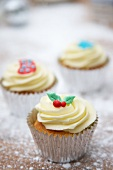 Cupcakes decorated with light frosting and marzipan decorations