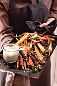 Root vegetables on a baking tray with a herb dip