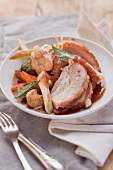 Sliced crispy roast pork with oven-roasted vegetables on a plate