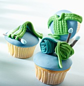 Three cupcakes with blue icing and marzipan knitting decorations