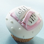 A cupcake decorated with a marzipan book