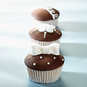 Three cupcakes with brown and white decorations