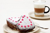 Small heart-shaped marble cakes with icing sugar and sugar hearts