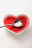 An empty heart-shaped bowl with a heart-shaped spoon