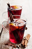 Two glasses of mulled wine with cinnamon, oranges and cloves