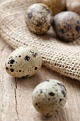 Quail's eggs on a wooden surface and on a jute sack