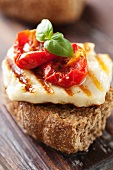 A wholemeal roll topped with grilled halloumi and sun-dried tomatoes